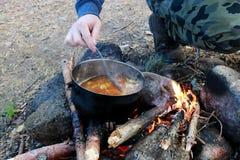 Варить на коле шевелить с ложкой супа в черноте от бака сажи стоковые фотографии rf