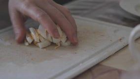 Варить салат краба Женская рука режет вареные яйца для ингредиента с ножом на доске Праздники придут скоро сток-видео