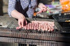 Варить сосиски на гриле Сосиски на гриле Девушка подготавливает сосиски на гриле стоковое изображение rf
