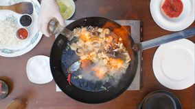 Варить с пламенем в сковороде на плите кухни Стоковое Фото