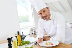 Варить шеф-повара подготавливая блюдо в кухне Стоковая Фотография RF