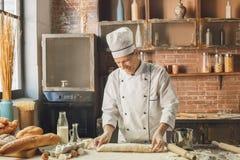 Варить шеф-повара хлебопекарни печет в профессионале кухни стоковое фото