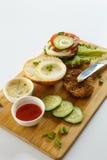 Варочный процесс бургера сандвича, ингридиенты на деревянной разделочной доске на деревянном столе против белой предпосылки, свеж Стоковое Фото