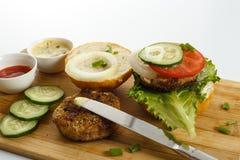 Варочный процесс бургера сандвича, ингридиенты на деревянной разделочной доске на деревянном столе против белой предпосылки, свеж Стоковое Изображение RF
