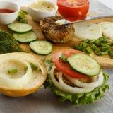 Варочный процесс бургера сандвича, ингридиенты на деревянной разделочной доске на деревянном столе против белой предпосылки, свеж Стоковое фото RF