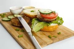 Варочный процесс бургера сандвича, ингридиенты на деревянной разделочной доске на деревянном столе против белой предпосылки, свеж Стоковые Фото