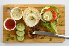 Варочный процесс бургера сандвича, inredients на деревянной разделочной доске на деревянном столе против белой предпосылки, свеже Стоковые Изображения