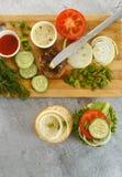 Варочный процесс бургера сандвича, inredients на деревянной разделочной доске на деревянном столе против белой предпосылки, свеже Стоковое фото RF