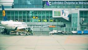 ВАРШАВА, ПОЛЬША - 25-ОЕ ДЕКАБРЯ 2017 Багаж загрузки к самолету Люфтганзы коммерчески на международном аэропорте Chopin акции видеоматериалы