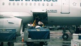 ВАРШАВА, ПОЛЬША - 25-ОЕ ДЕКАБРЯ 2017 Почта загрузки на самолет Люфтганзы на международном аэропорте Chopin сток-видео