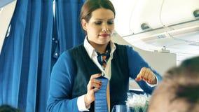 ВАРШАВА, ПОЛЬША - 25-ОЕ ДЕКАБРЯ 2017 Стюардесса служит напитки к пассажирам на авиалайнере KLM сток-видео