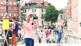 ВАРШАВА, ПОЛЬША - 10-ОЕ ИЮНЯ 2017 Белокурая женщина делает фото с ее камерой Nikon DSLR в туристском месте - старом городке Стоковое Изображение RF