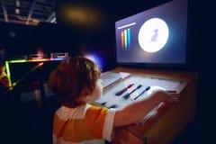 ВАРШАВА, ПОЛЬША - 20-ое июня 2019: Любопытный ребенк исследуя характеристики света в центре науки Коперника в Варшаве, стоковые изображения rf