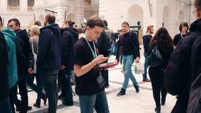 ВАРШАВА, ПОЛЬША - 4-ОЕ МАРТА 2017 Молодой участник выставки робототехники держа компьтер-книжку и сотовый телефон видео 4K видеоматериал