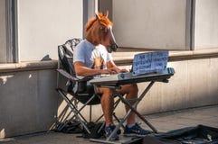 Варшава, Польша 1-ое октября 2016 - Гай в маске лошади играя рояль стоковые изображения