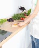 варящ вырезывание огурца съешьте женский портрет жизни кухни дома девушки подготовляя довольно усмехаться что-то стоя к детенышам Стоковое фото RF