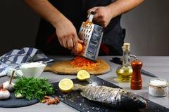 Варящ карпа заполненного с овощами руками шеф-повара, протрите морковей на терке Варить рецепт Подлинное изображение образа жизни стоковое изображение rf