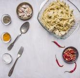 Варящ макаронные изделия концепции готовые с индюком в cream соусе с чесноком, специи ложки вилки перцев красного chili в стеклян Стоковое фото RF