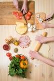 Варящ пиццу дома Заполняя пицца с ингридиентами Взгляд сверху стоковая фотография