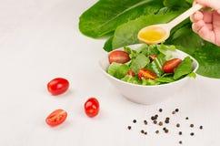 Варящ свежий салат весны зеленых цветов, куски томата вишни на белой деревянной предпосылке, копируют космос Рука держит ложку и  Стоковые Фотографии RF
