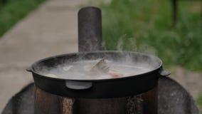 Варящ суп рыб outdoors, на поверхности пены воды и обильного пара, лето видеоматериал