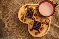 Вафли и печенья шоколада в деревянном подносе в форме сердца и чашке горячего шоколада стоковое фото