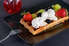 Вафли с ягодами и сливк на плите Стоковая Фотография