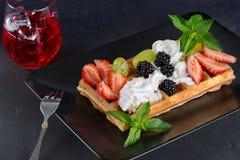 Вафли с ягодами и сливк на плите Стоковые Изображения
