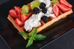 Вафли с ягодами и сливк на плите Стоковые Фото