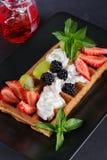 Вафли с ягодами и сливк на плите Стоковое фото RF
