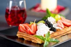 Вафли с ягодами и сливк на плите Стоковое Изображение