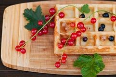 Вафли украшенные с красными смородинами на деревянной предпосылке Стоковые Фото