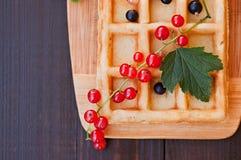 Вафли украшенные с красными смородинами на деревянной предпосылке Стоковые Фотографии RF