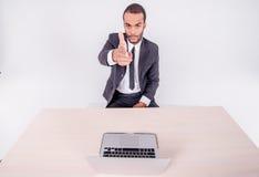 Ваши паспределения Усмехаясь африканский бизнесмен сидя на столе дальше Стоковые Изображения