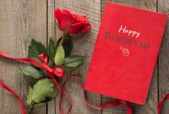 Валентайн карточки s Красная роза и тетрадь красного цвета с желаниями на деревянной доске Стоковое Изображение