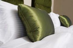 Валики, зеленые подушки на кровати в гостиничном номере Стоковое Фото