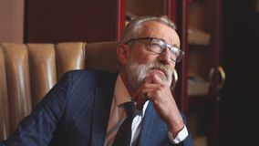 Введенный в моду портрет бизнесмена сидя в кресле на офисе акции видеоматериалы