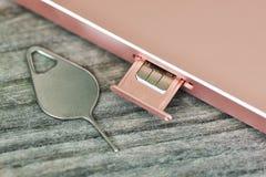 Введите SIM-карту на смартфоне с металлическим штырем на деревянном столе или предпосылке стоковое изображение