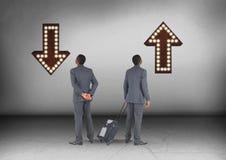 Вверх или вниз стрелок при бизнесмен смотря в противоположных направлениях Стоковая Фотография
