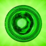 Вверх ногами зеленая пивная бутылка на зеленой предпосылке стоковая фотография