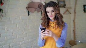 Введите даму в моду используя smartphone, интересуя на фоне белой стены видеоматериал
