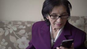 Введите бабушку в моду в ее 70s используя Iphone, усмехаться, смотря в сторону видеоматериал