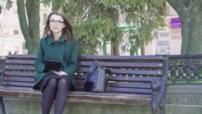 Введите девушку в моду сидя на стенде, используя таблетку на улице 4K акции видеоматериалы