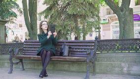 Введите девушку в моду сидя на стенде, принимая фото с таблеткой внешней 4K видеоматериал