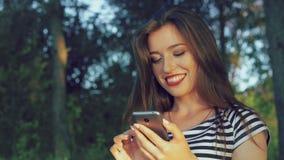 Введите девушку в моду смотря на телефоне и касающих волосах в парке 4K акции видеоматериалы
