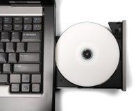 Вводить КОМПАКТНЫЙ ДИСК/DVD в привод компьтер-книжки стоковое фото rf