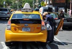 вводя желтый цвет женщины таксомотора nyc стоковое изображение rf