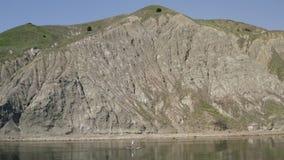 Вдоль берега против предпосылки горы хлебают плавая человек Мероприятия на воде акции видеоматериалы
