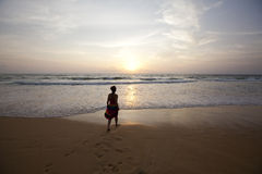 вдоль гулять захода солнца девушки пляжа Стоковые Изображения RF