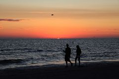 вдоль гулять захода солнца пар пляжа стоковое фото rf